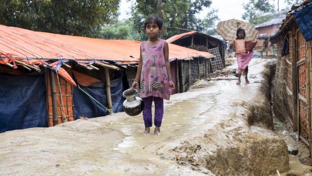 Mädchen steht mit Wasserkrug auf überschwemmter, matschiger Strasse.