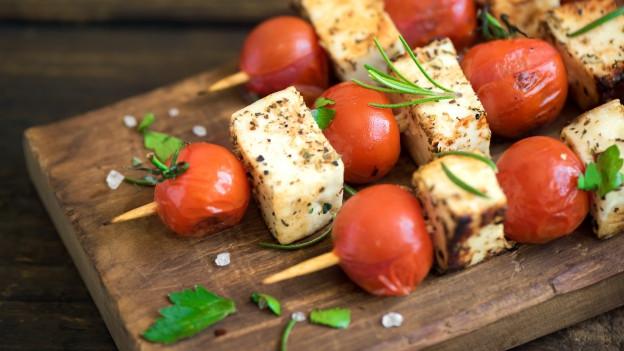 Halloumi-Tomaten-Spiess auf einer Holzplatte serviert