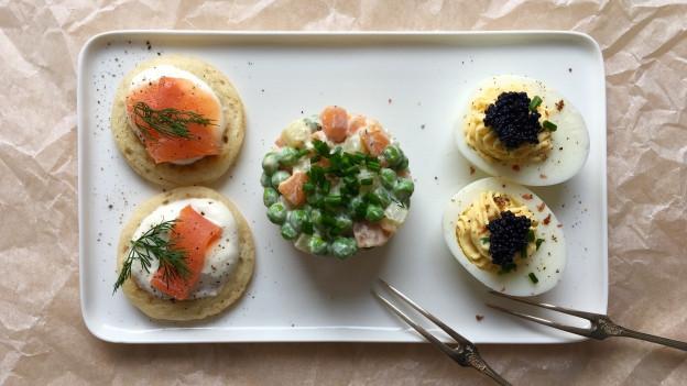 Vorspeiseplättli mit russischen Spezialitäten - russische Eier, russischer Salat, Blini mit Sauerrahm und Lachs.