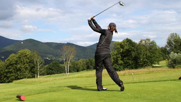 Frau beim Schlag im Golf.