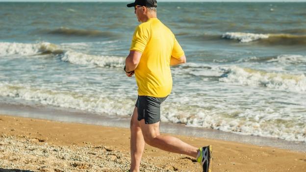 Ein Mann rennt am Strand.