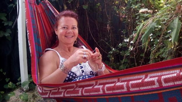 Monika Greter sitzt in der Hängematte und häkelt ein Strandbikini