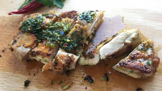Aufgeschnittener knusprig gebratener Hühnchenschenkel ohne Knochen mit asiatischer Salsa.