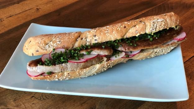 Gegrillte Bratwurststreifen im Brot als Sandwich zubereitet.