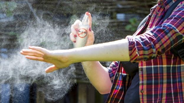 Frau sprayt Mückenspray ein
