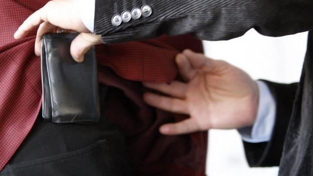 Dieb zieht Opfer Portemonnaie aus der Tasche.