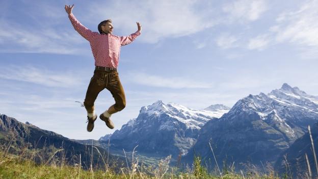 Mann springt vor Berg in die Luft.
