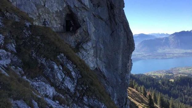 Eine Höhle im Fels, dahinter der Thunersee im Blick.