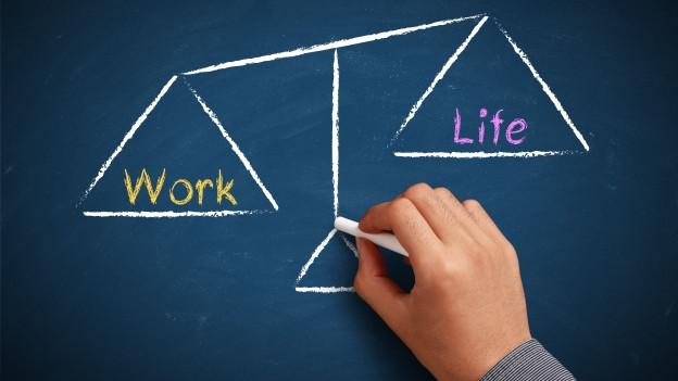 """Eine Waage zeigt auf einer Seite das Wort """"Work"""", auf der anderen Seite das Wort """"Balance""""."""