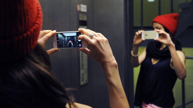 Eine Frau macht im Lift ein Selfie in einem Spiegel.