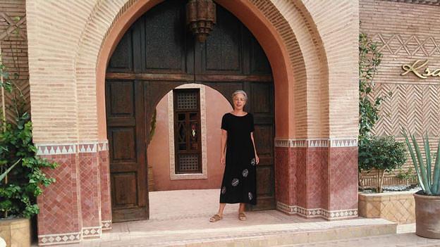 Eine Frau steht vor einem grossen Eingang zu einem marokkanischen Haus.