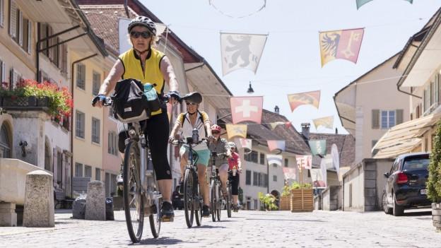 4 Velofahrerinnen auf ihren Fahrräder in einer Stadt.