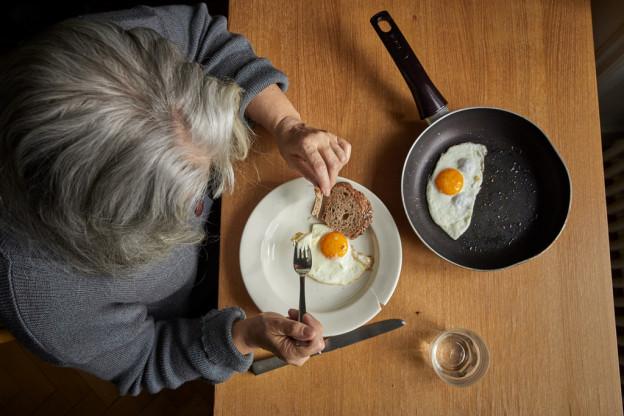 Eine ältere Frau isst Spiegeleier in ihrer Wohnung in der Zentralschweiz