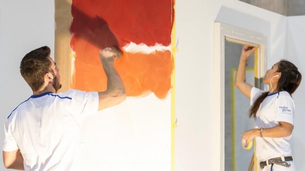 Eine Flächenmalerin und ein Flächenmaler streichen eine Wand.