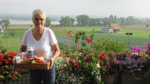 Frau mit einem Körbchen mit Mehl, Butter, Äpfeln.