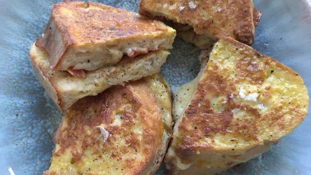 Vier French Toasts mit Käse und Schinken auf einem Teller.