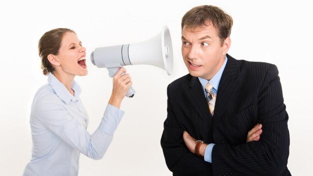 Frau schreit mit Megafon in Ohr eines Mannes