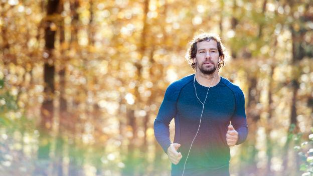Jogger mit Kopfhörern im herbstlichen Wald.