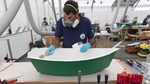 Lehrling arbeitet an einem Boot.