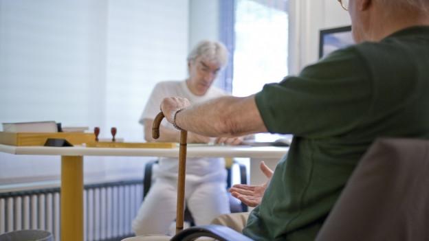 Arzt und Patient im Gespräch am Tisch