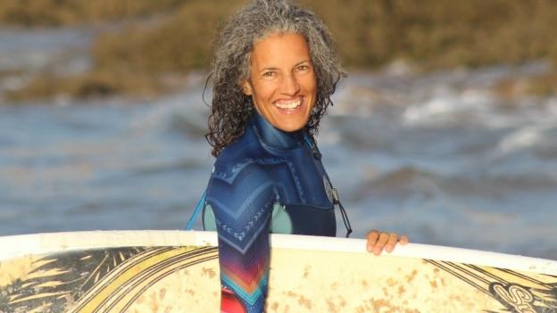 Lisa Kauer posiert mit ihrem Surfbrett am Strand.