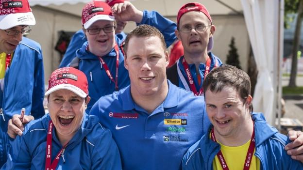 Schwingerlegende Matthias Sempach, umringt von Athleten mit kognitiver Behinderung
