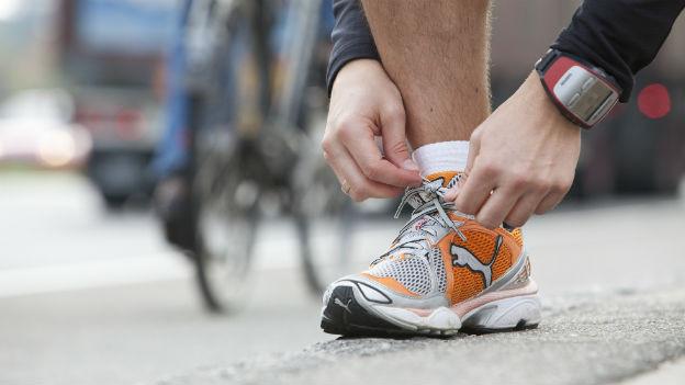 Ein Mann bindet sich die Laufschuhe.