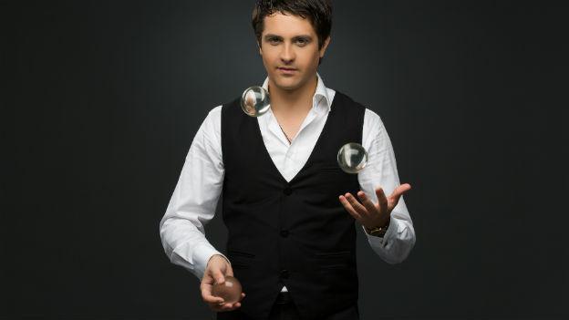 Ein Mann jongliert mit drei Kugeln.