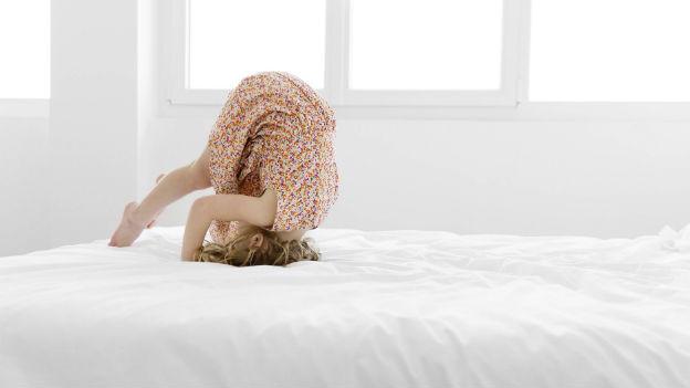 Mädchen macht Purzelbaum auf Bett.