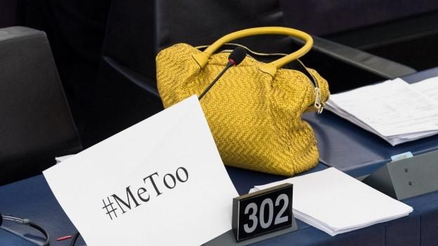 Ein MeToo Plakat neben einer gelben Handtasche auf einem Parlamentspult.