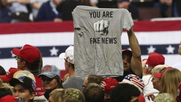 Ein Mann hält ein T-Shirt mit der Aufschrift 'Fake News' hoch