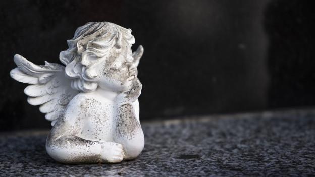Ein Gips-Engelchen sitzt auf einem Grab.