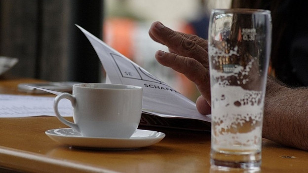 Ein ausgetrunkenes Bier und ein Espresso