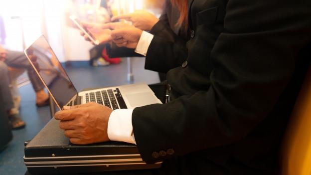 Laptop steht auf Aktenkoffer, der auf den Beinen eines Zugfahrenden ist.