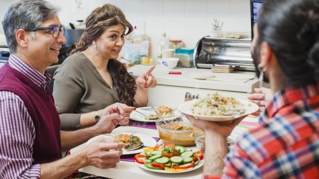 Drei Leute essen an einem Tisch.