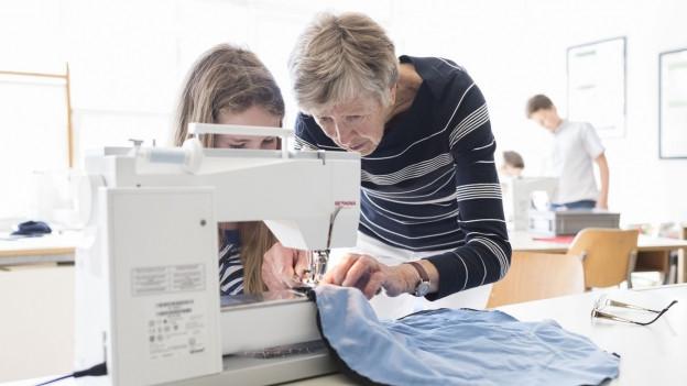 pensionierte Frau hilft in Handarbeitsunterricht mit