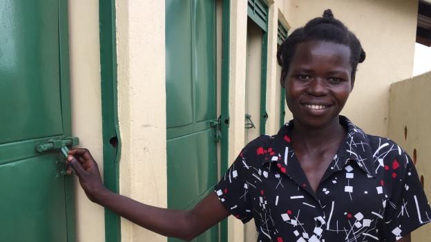 Die einheimische Hygiene-Assistentin Molly Azikuru steht neben einer neu gebauten Toilette von «Heks».