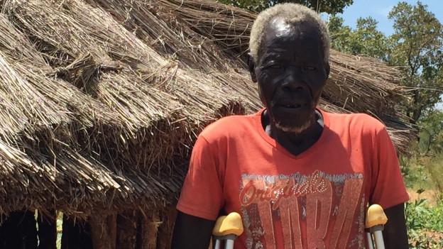 Mann in orangem T-Shirt und grauen Haaren steht mit Krücken vor seiner Hütte aus Holzstämmen und Strohdach.