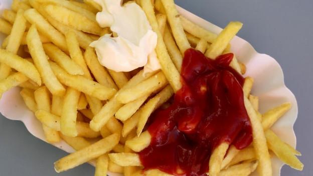 Eine weisse Schale Pommes Frites mit Mayonnaise und Ketchup