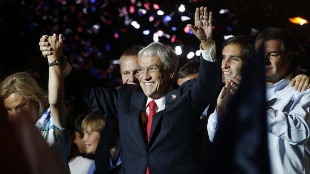 Sebastián Piñera feiert seinen Wahlsieg in Chiles Hauptstadt Santiago, die Arme in der Luft, die Frau an der rechten Hand, er lacht und ist im dunklen Anzug, um ihn herum Leute und hinter ihm buntes Konfetti.