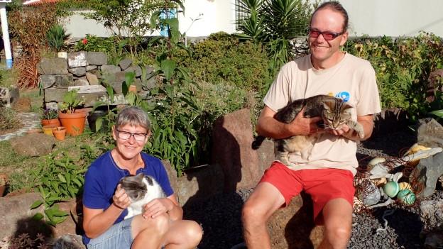 Franziska und Christian mit ihren Katzen auf dem Arm.
