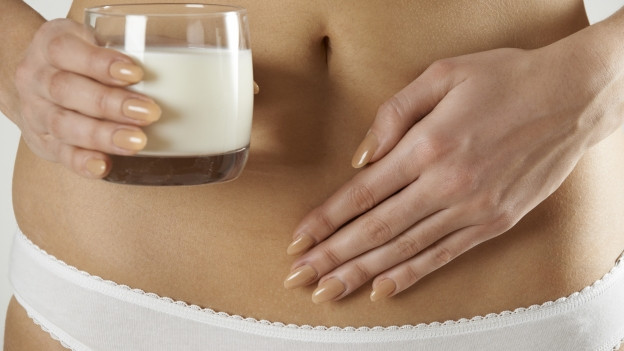 Eine Frau hält ein Glas Milch in der Hand, die andere Hand hält sie vor den Bauch.