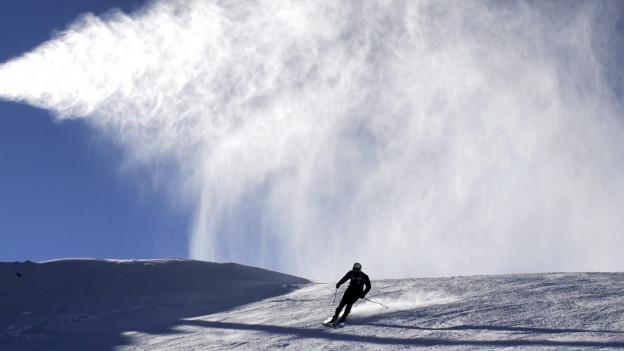 Ein Skifahrer fährt alleine auf einer breiten Piste. Eine Beschneiungsanlage wirbelt Schnee auf die Piste.