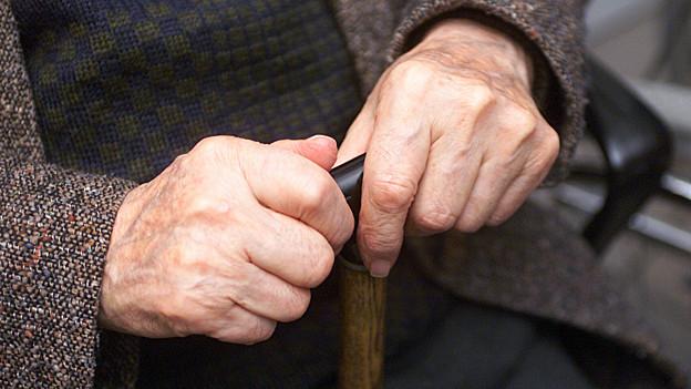 Hände eines alten Mannes mit Stock