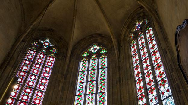 Ein farbiges Kirchenfenster von innen fotografiert.