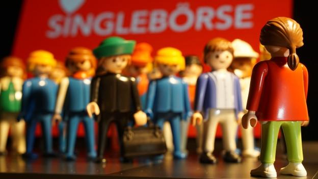 Playmobilmännchen vor einer Tafel 'Singlebörsen'