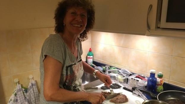 Eine Frau steht in der Küche und schneidet Fleisch.