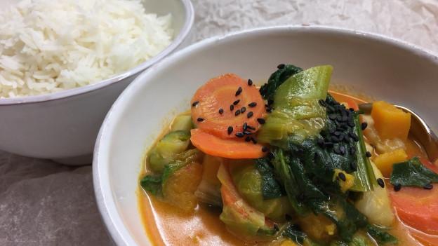 Thai-Curry mit Wintergemüse in einem Schälchen und eine Schale Reis.