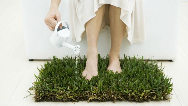 Frau steht barfuss auf Rasen.