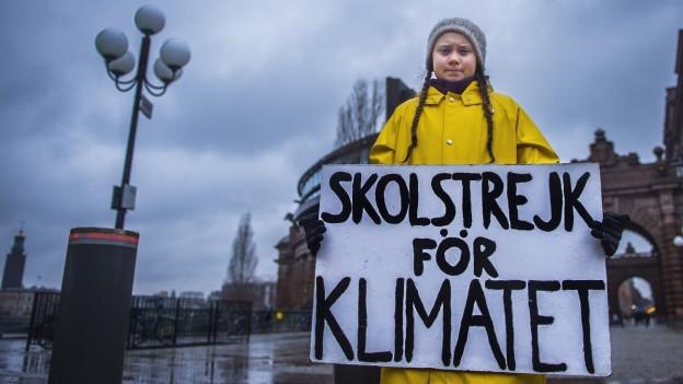 Die Schülerin Greta Thunberg mit einem Protesplakat in den Strassen von Stockholm